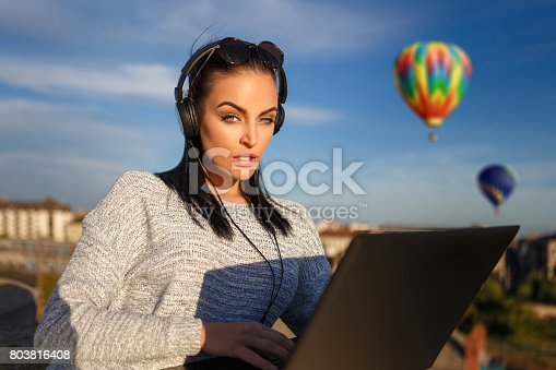 istock Woman ordering hot air balloon tour by laptop outdoor 803816408