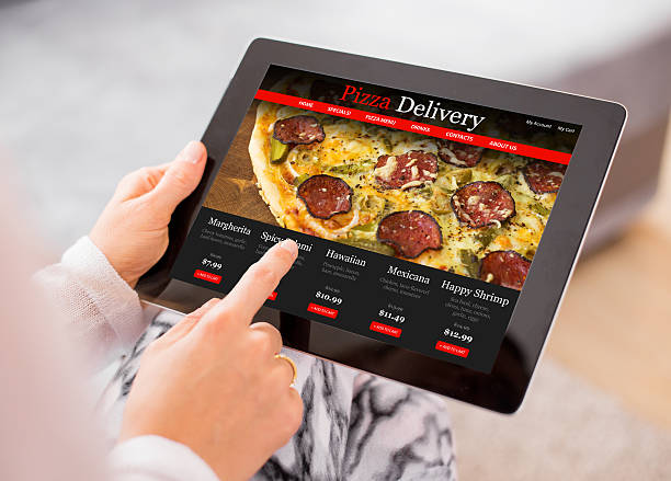 Woman ordering pizza online stock photo
