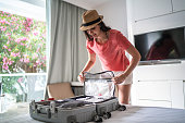 Woman organizing her luggage at hotel room