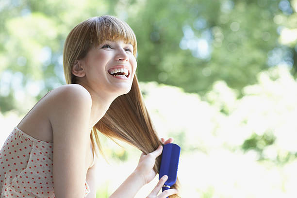 Woman outdoors brushing hair and laughing stock photo