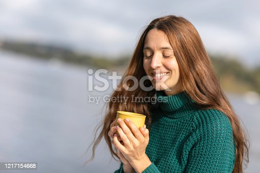 A happy woman outdoors in the sun, by a lake. Blinking, holding a mug a coffee.