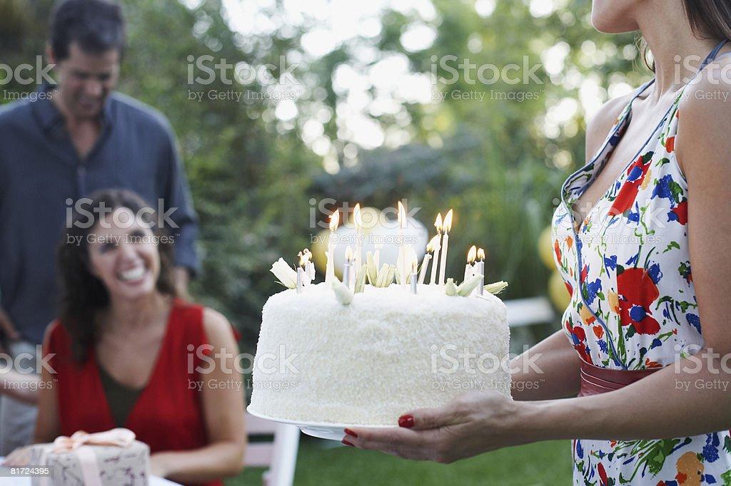 Mujer al aire libre con un pastel de cumpleaños para un sonriente pareja - foto de stock