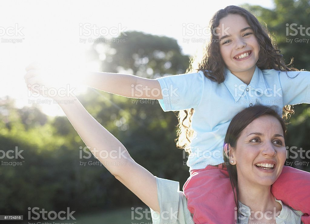 Woman outdoors giving young girl shoulder ride and smiling royalty-free stock photo