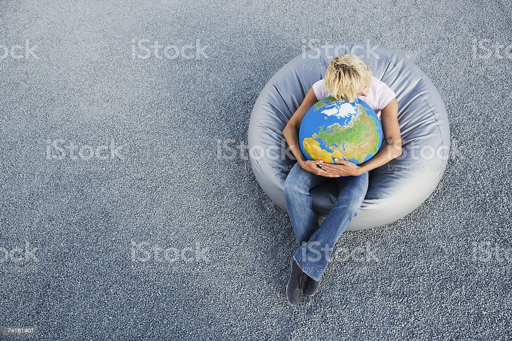 Woman outdoors in beanbag chair holding globe royalty-free stock photo