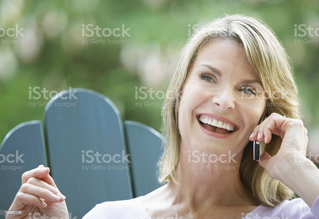 Woman outdoors in yard on cellular phone laughing 免版稅 stock photo
