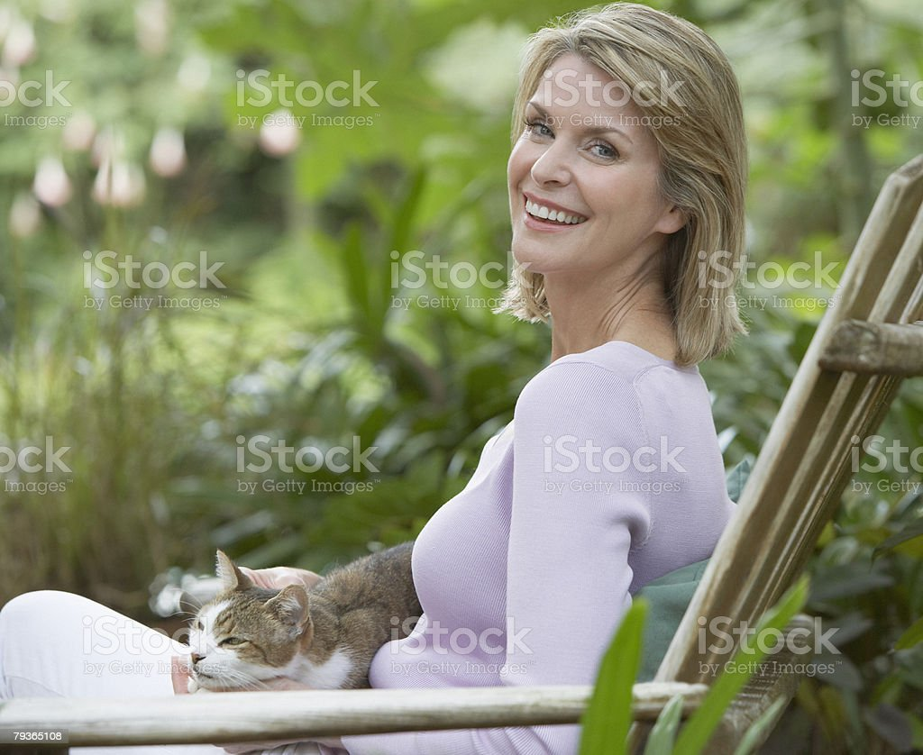 Woman outdoors in yard with cat on her lap stock photo