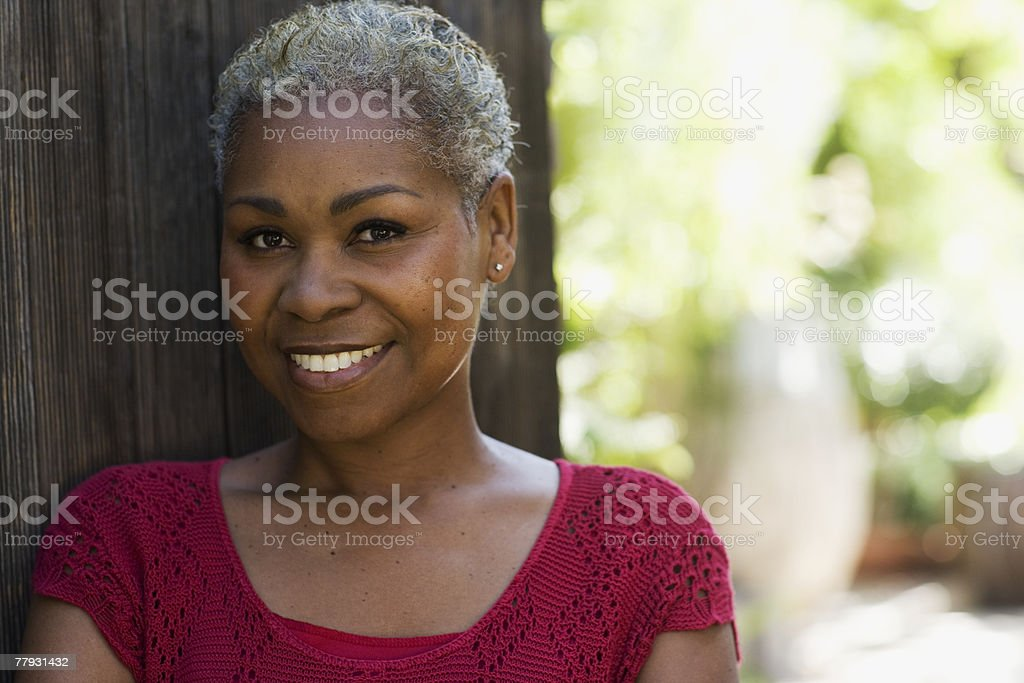 Woman outdoors leaning against a wooden fence smiling stock photo