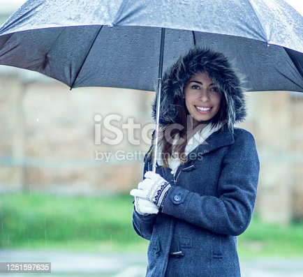 Portrait of a happy Latin American woman outdoors on a rainy day wearing warm clothes and using an umbrella while looking at the camera smiling