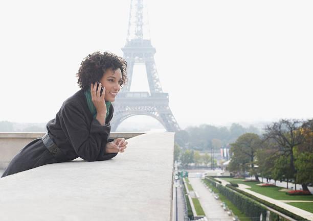 femme à l'extérieur sur son téléphone portable près de la tour eiffel - france photos et images de collection