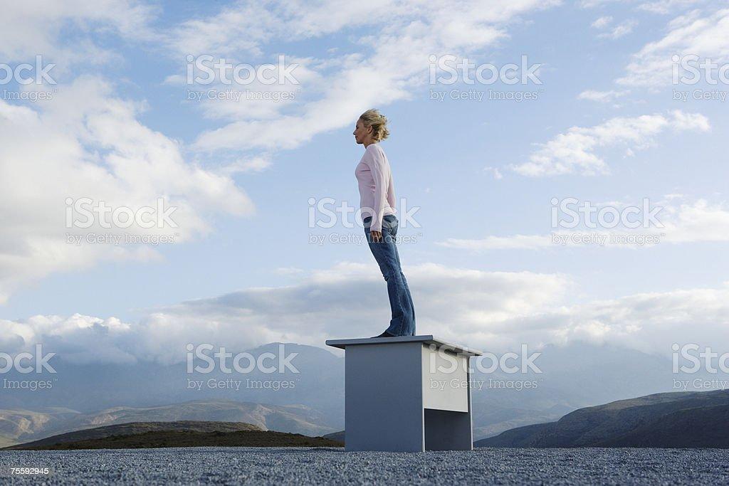 Mulher de pé em uma mesa ao ar livre para o vento Inclinar-se foto de stock royalty-free