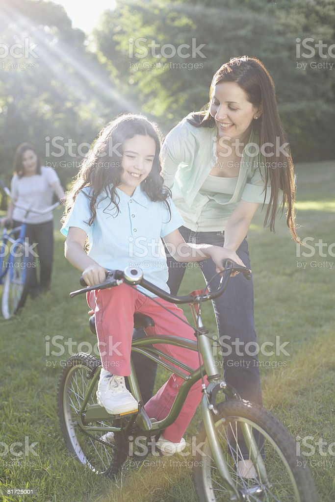 Woman outdoors teaching smiling young girl to ride bicycle stock photo
