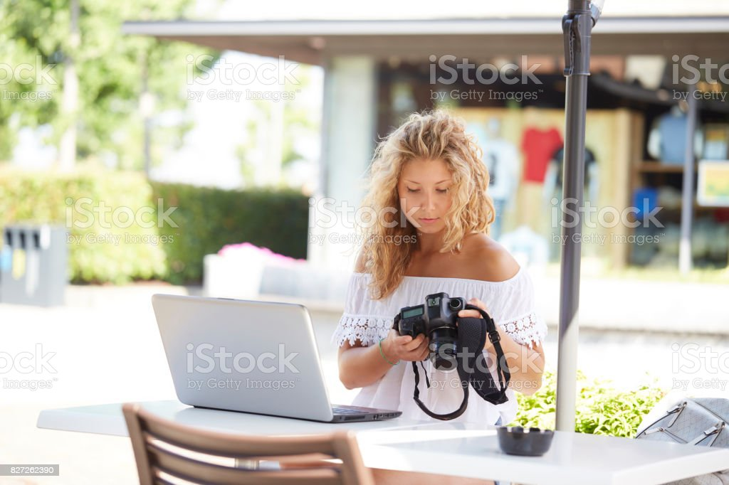 woman outdoors using a digital reflex to take pictures and check on her laptop what she made stock photo