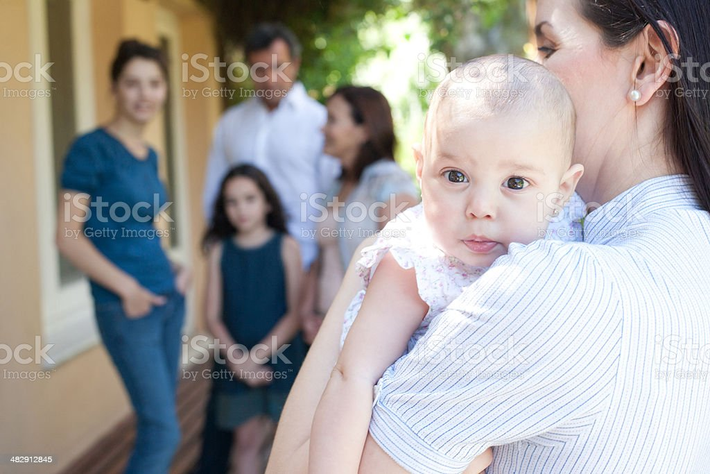 Woman outdoors with baby and family in background stock photo