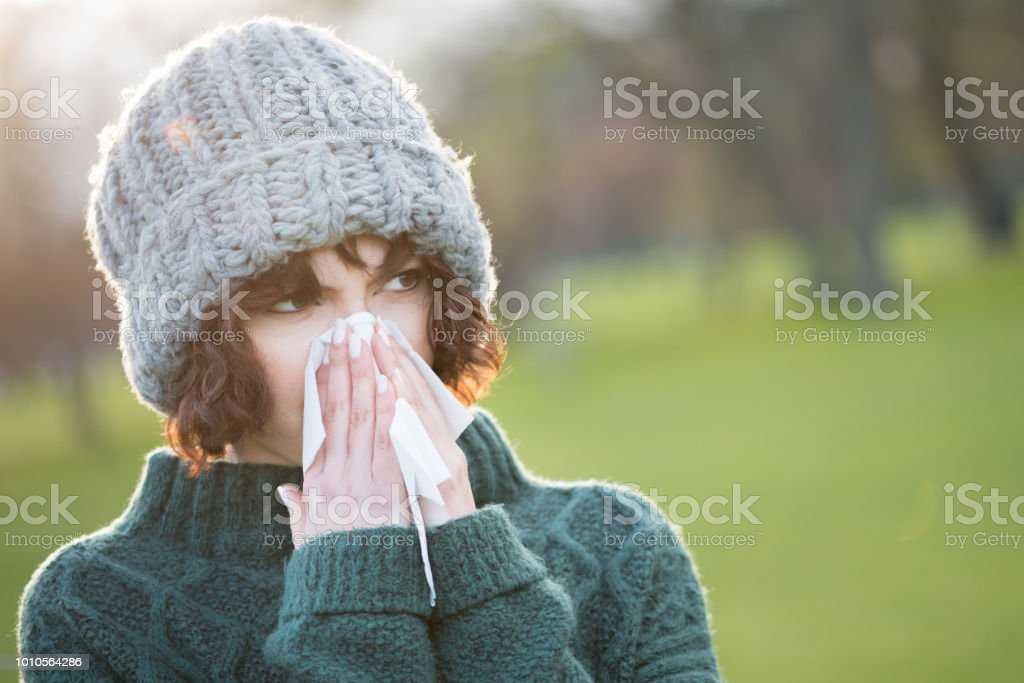 Woman Outdoors with Cold or Flu Blowing Nose stock photo
