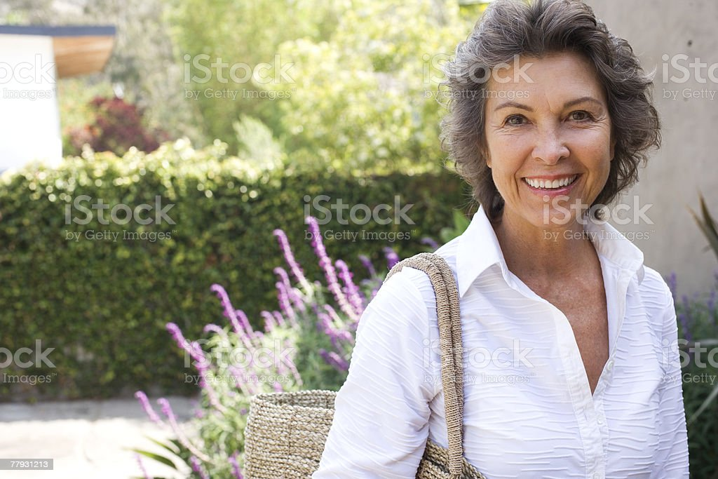 Woman outside home with large purse smiling stock photo