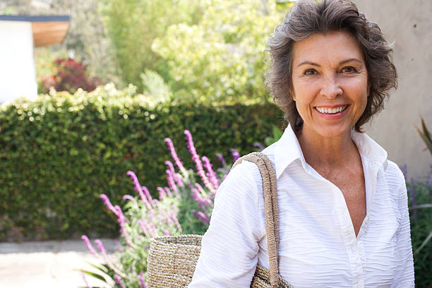 woman outside home with large purse smiling - vrouw 60 stockfoto's en -beelden
