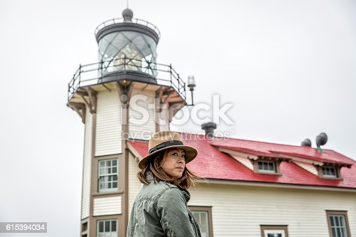 Stock photo of a woman wearing a fedora hat outside of a lighthouse on a foggy day