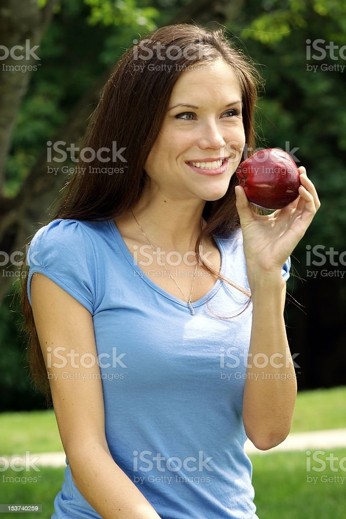 Woman Outside Park Eating Raw Food Red Delicious apple stock photo