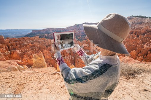 istock Woman over beautiful red canyon using a digital tablet; connection in remote locations, people using technology in nature 1146814406