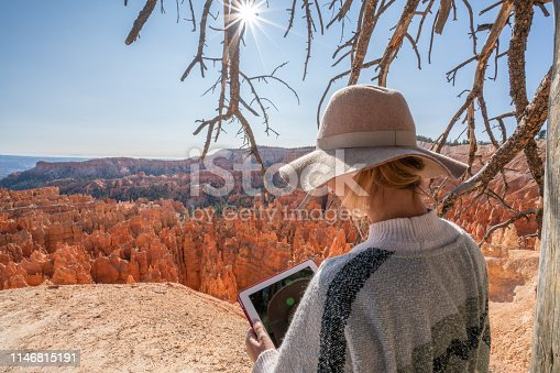 istock Woman over beautiful red canyon using a digital tablet; connection in remote locations, people using technology in nature 1146815191