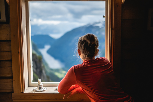 Young woman overlooking fjord in Norway while opening window.