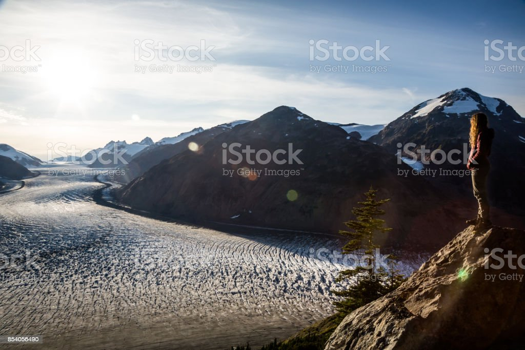 Woman overlooking Salmon Glacier with sun flare stock photo