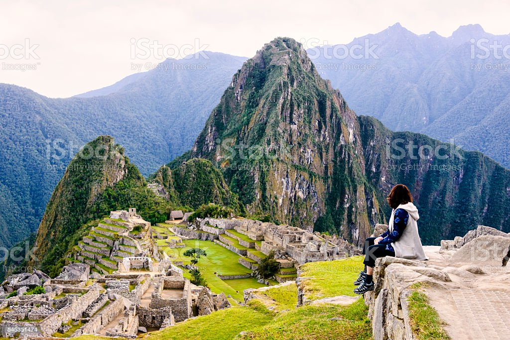 Woman overlooking the Inca ruins of Machu Picchu stock photo