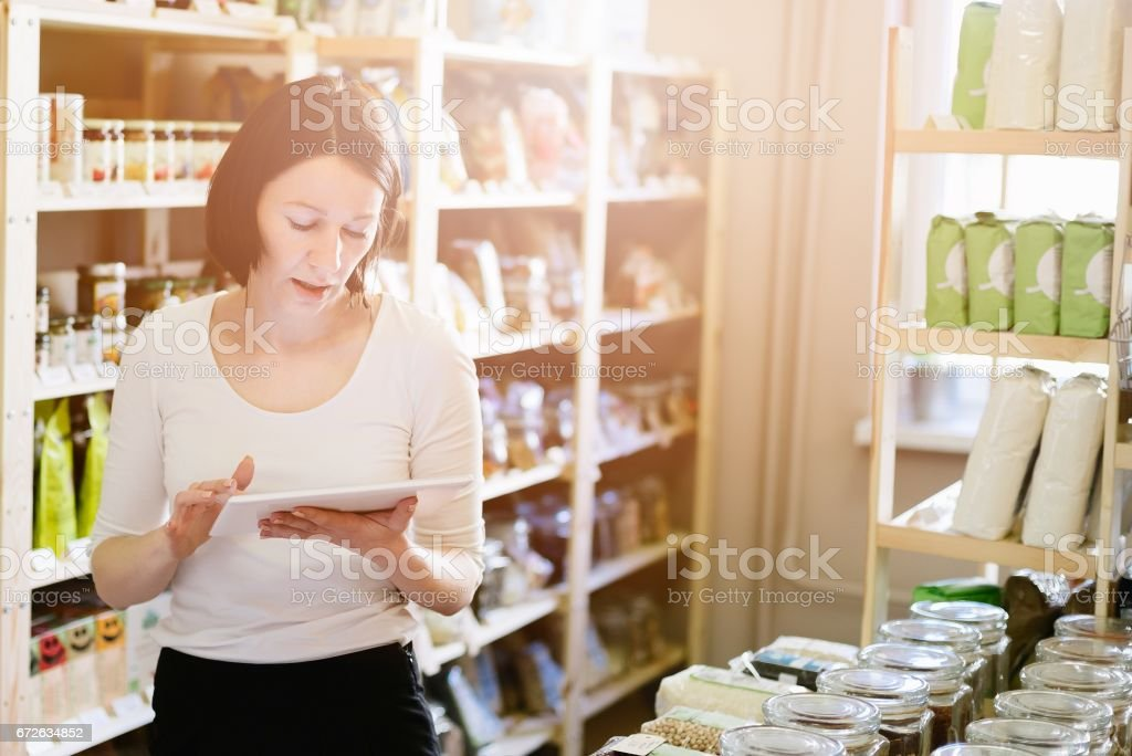 Woman owner of store with healthy food ordering products with a tablet bildbanksfoto