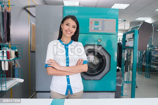 Woman owning a laundry service shop and looking confident looking at the camera with arms crossed