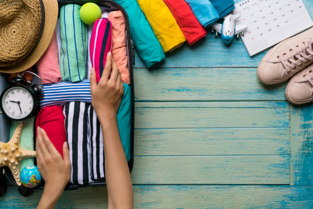 woman packing a luggage for a new journey and travel for a long weekend stock photo