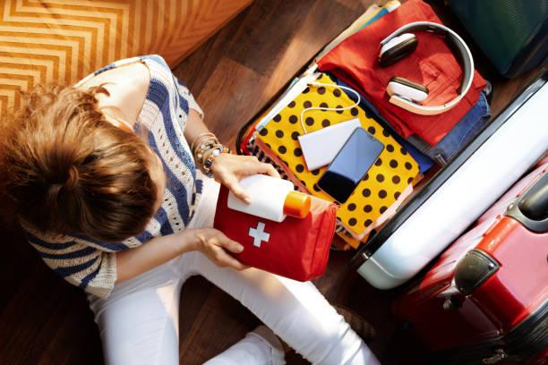 오픈 여행 가방에 응급 처치 키트와 spf를 포장하는 여성 - 짐 싸기 뉴스 사진 이미지