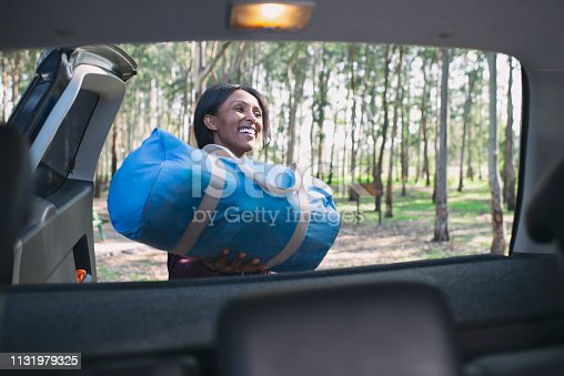 African woman loading blue bag into the car trunk. Happy young woman packing / unpacking luggage from the car trunk.