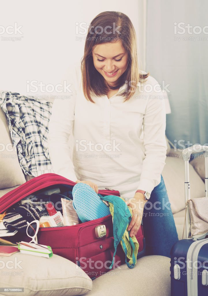 Smiling woman preparing to depart for holiday at home