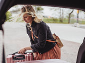 Woman packing her car with luggage bags ready for trip\nModern photo taken outdoors of woman and suitcases by car