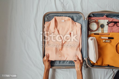 Hands of unrecognisable woman putting elegant blouse in a suitcase.