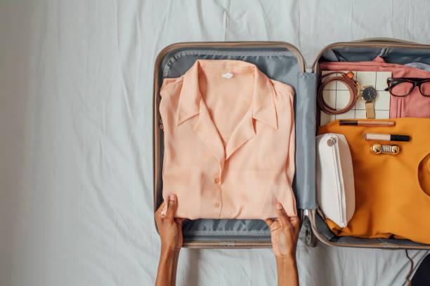 가방에 옷을 포장하는 여성 - 짐 싸기 뉴스 사진 이미지