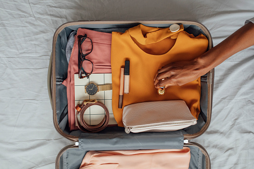 Hands of unrecognisable woman putting stuffs in her suitcase.