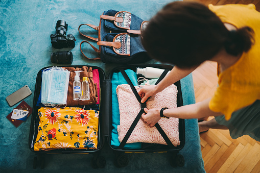 Woman packing suitcase for summer travel, including face masks and airplane travel-sized antibacterial hand gels