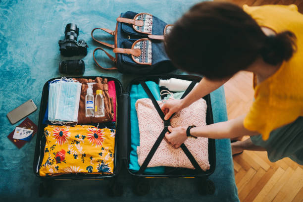 Woman packing suitcase for travel stock photo