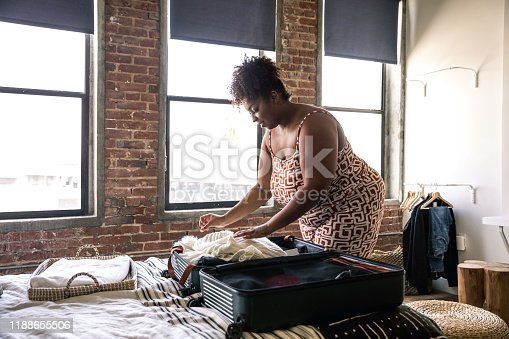 Woman preparing the suitcase for leaving the house before a travel. She's packing on the bed