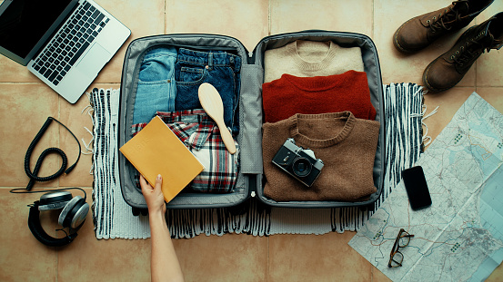 Woman packs winter themed suitcase for autumn holiday. Vacation preparation, careful bag packing. Millennial generation z travel blogger pack suitcase with social media vintage camera, sweater, laptop