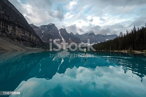 istock Woman paddle-boards across Moraine Lake, Banff NP 1245753598