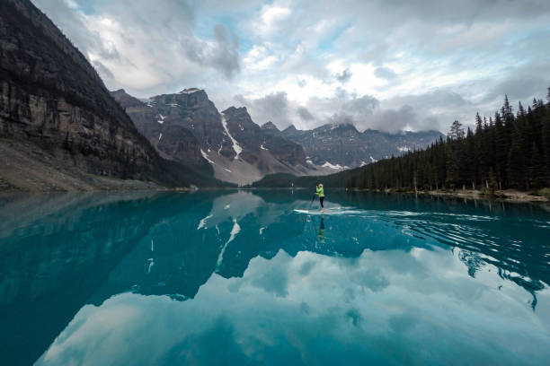 Woman paddle-boards across Moraine Lake, Banff NP stock photo