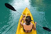 Woman paddles yellow kayak in the lake with turquoise water. Top view kayak in the lake with turquoise water. Top view