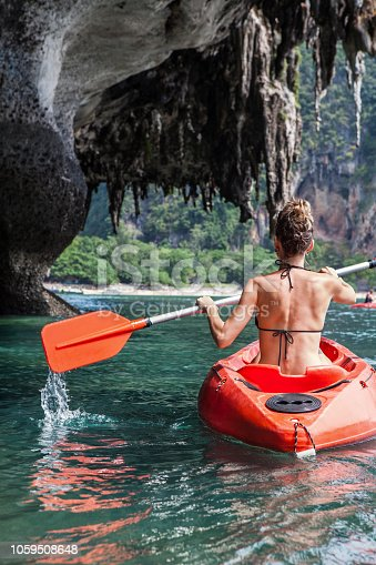 istock Woman paddles kayak in the tropical sea 1059508648