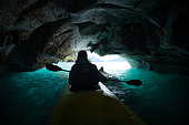 Woman paddles kayak inside the marble cave located on the General Carrera lake in Chile