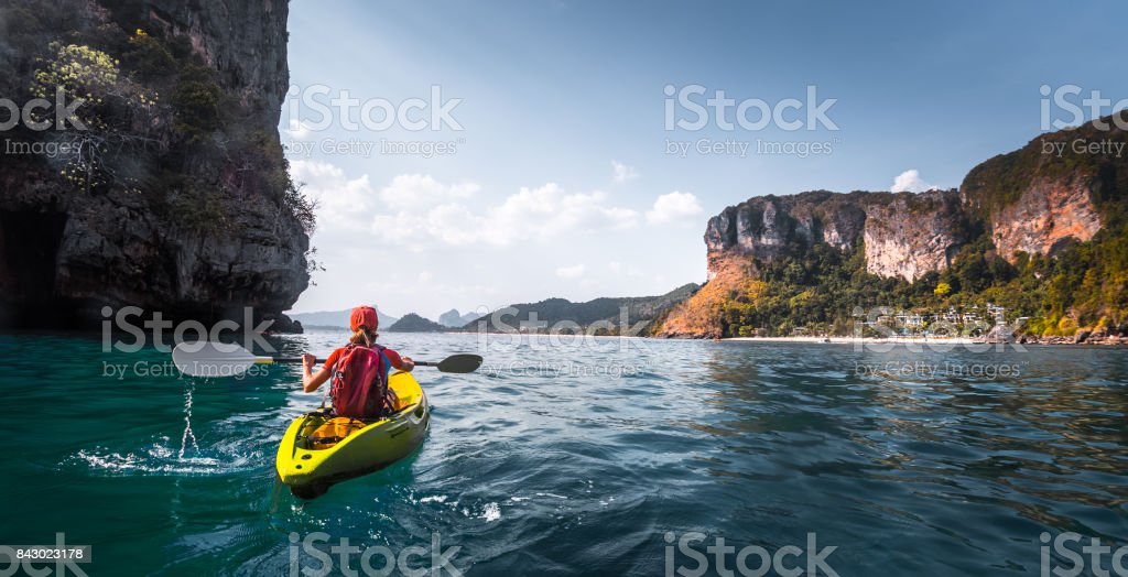 Woman paddles kayak stock photo