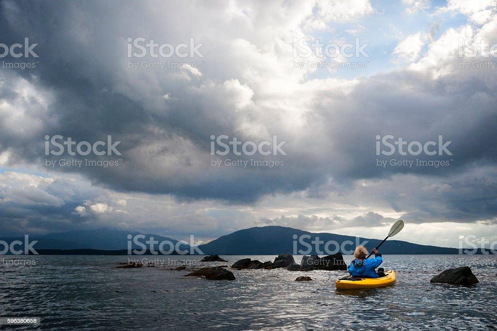 Woman paddles kayak under dramatic clouds stock photo