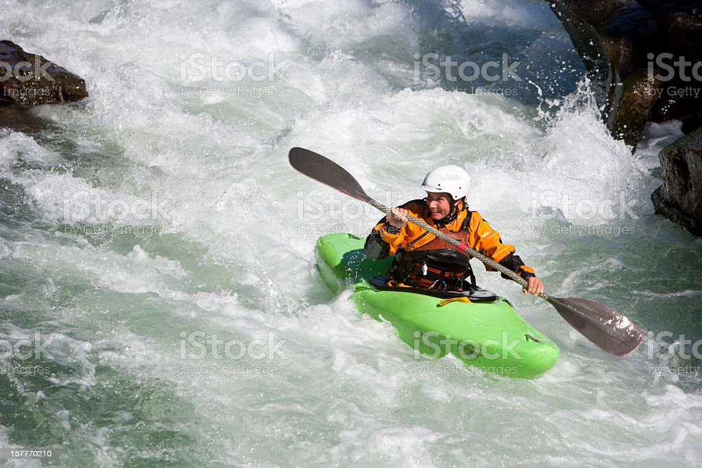 Woman Paddling a Whitewater Kayak on a Montana River. royalty-free stock photo