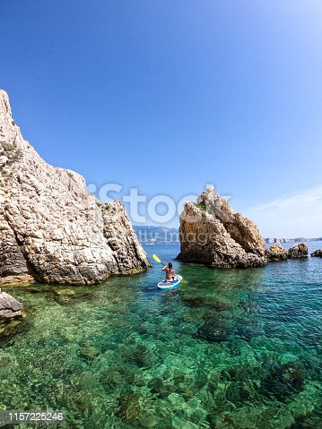 Woman paddling between rocks